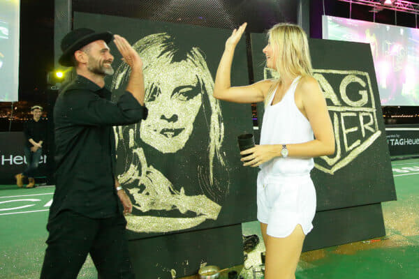 SINGAPORE - OCTOBER 22: Speed painting artist, Michael Raivard (L) high-five with Maria Sharapova after the speed painting contest infused with gold dust during the Maria Sharapova Exhibition Match at Clifford Pier, Fullerton Bay Hotel on October 22, 2015 in Singapore. (Photo by Suhaimi Abdullah/Getty Images For TAG Heuer) *** Local Caption *** Maria Sharapova; Michael Raivard