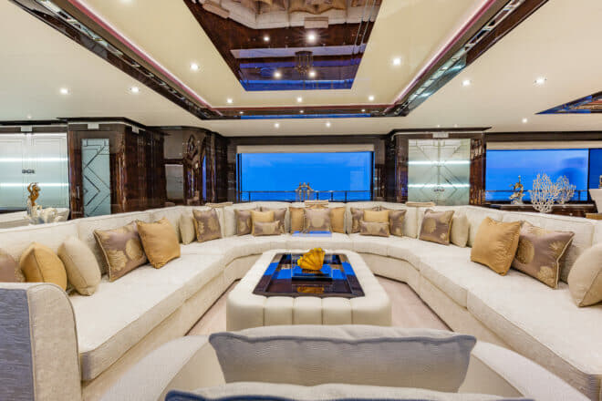 On the main deck, the saloon is dominated by a huge U-shaped couch, with large windows either side