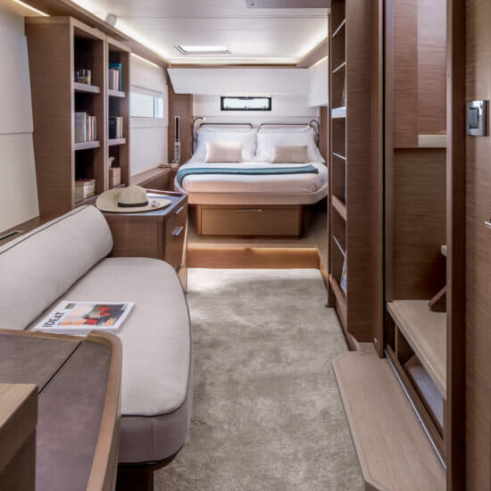 The owner's suite is truly luxurious, with a large bed, double couch, central desk area, lots of storage, stylish Walnut finish and elongate