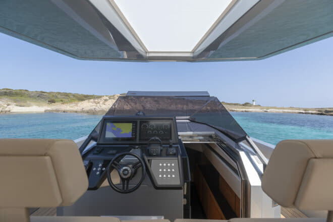 The 48 Wallytender helm station features two Garmin display screens and two twin benches with flip-up seats