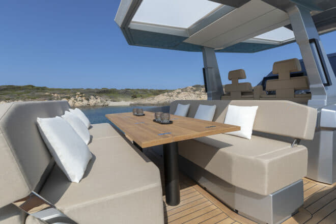 Situated aft of the helm station and the outdoor galley, the social heart of the boat is the dining table and two sofas, which feature adjustable backrests