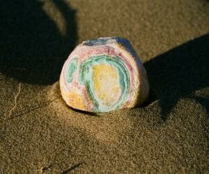 a photo of a colourful stone on the sand from Lina Scheynius photo-essay for Tabayer jewelry Tabayer jewellery