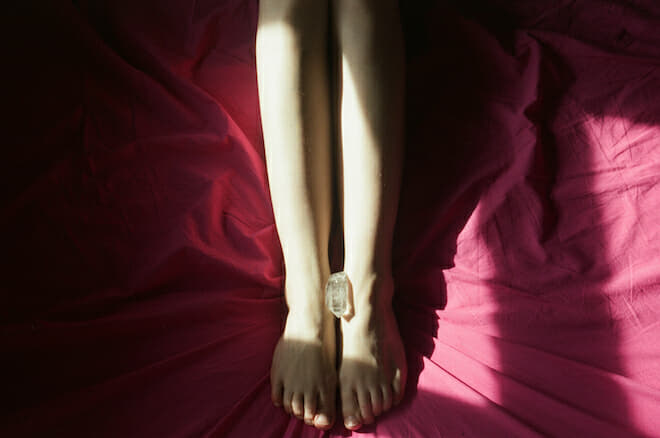 a photo of a piece of crystal is placed between a woman's feet who is in bed on red bedsheets from Lina Scheynius photo-essay for Tabayer jewelry Tabayer jewellery